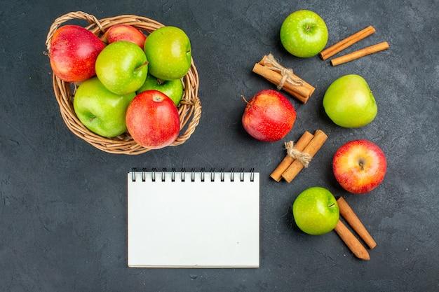 Вид сверху свежие яблоки в плетеной корзине, блокнот с палочками корицы на темной поверхности