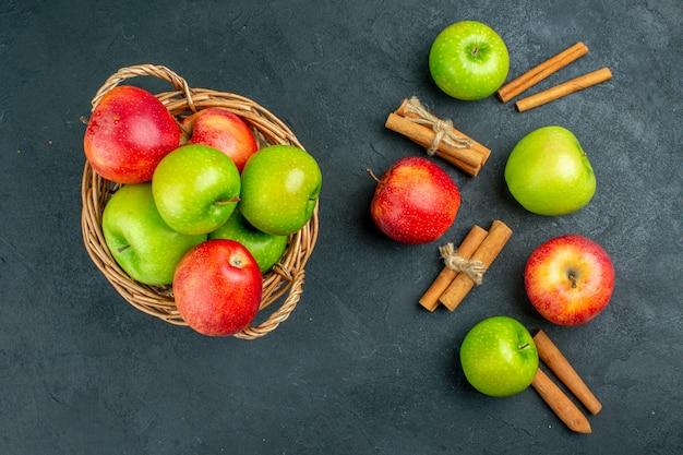 Вид сверху свежие яблоки в плетеной корзине, палочки корицы на темной поверхности