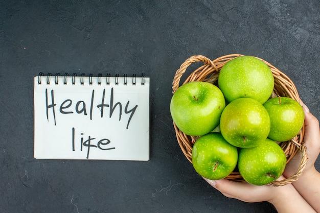 Вид сверху свежие яблоки в плетеной корзине здорового образа жизни, написанные в блокноте на темной поверхности