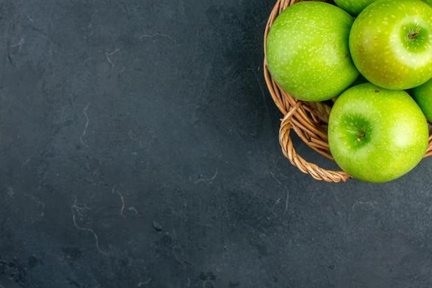 空きスペースのある暗い表面の籐のバスケットの上面図新鮮なリンゴ