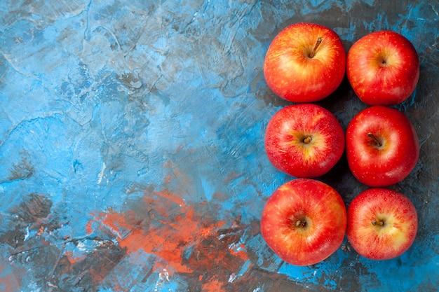 Vista dall'alto mele fresche allineate su sfondo blu, dieta salutare matura, colore libero