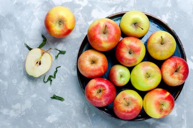 가벼운 책상 위의 신선한 사과를 볼 수 있습니다.