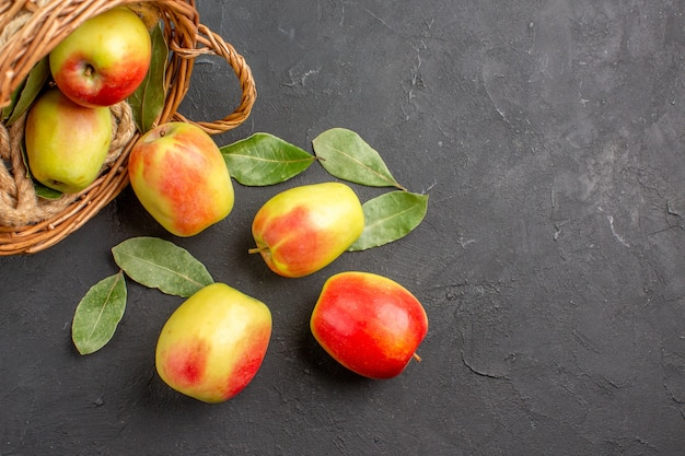 灰色のテーブルのバスケットの中の新鮮なリンゴの熟した果実の上面図熟した新鮮な果実