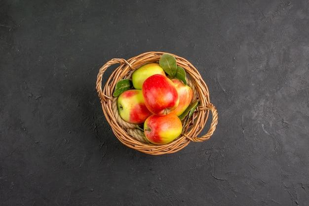 灰色のテーブルのバスケットの中の新鮮なリンゴの熟した果実の上面図熟した果実の新鮮な