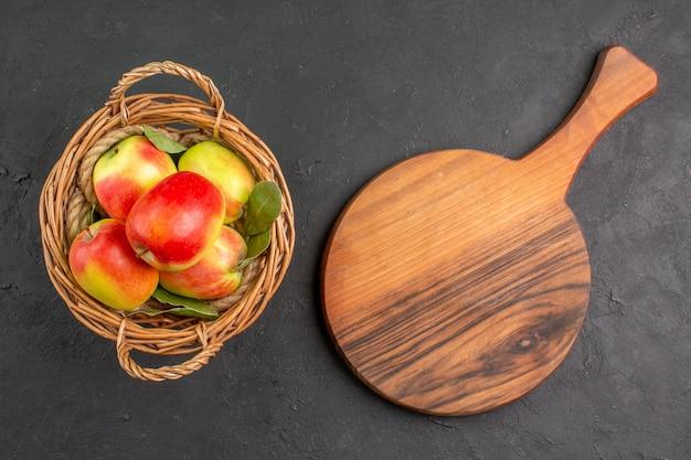 灰色の机の上のバスケットの中の新鮮なリンゴの熟した果実の上面図熟した果実の新鮮な