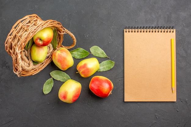 灰色の床のバスケットの中の新鮮なリンゴの熟した果実の上面図熟した新鮮な果実