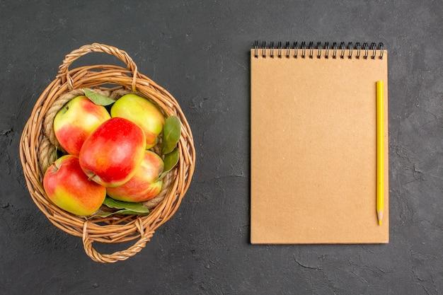 灰色の床のバスケットの中の新鮮なリンゴの熟した果実の上面図熟した果実の新鮮な