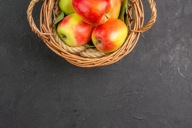 灰色のテーブルの上のバスケットの中の新鮮なリンゴの熟した果物の上面図果物の新鮮な熟した