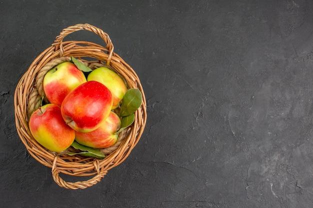 Вид сверху свежие яблоки спелые фрукты внутри корзины на сером столе свежие спелые фрукты