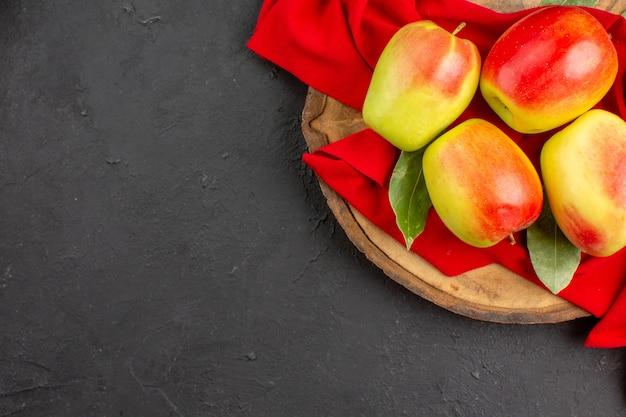 Вид сверху свежие яблоки спелые фрукты на красной ткани и серый стол свежие спелые фрукты