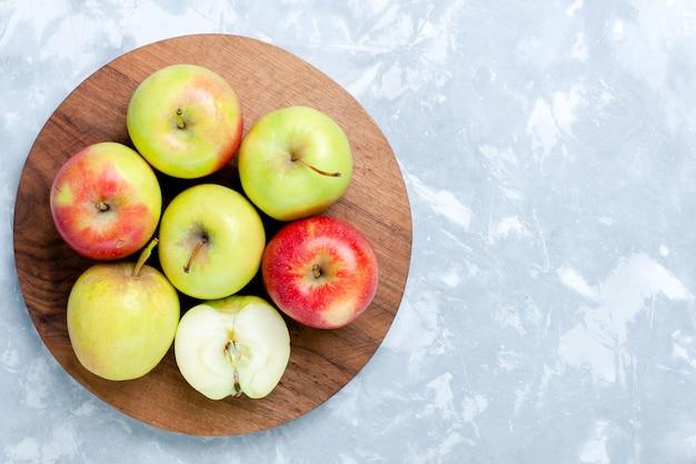 Top view fresh apples ripe mellow fruits on the light-white desk