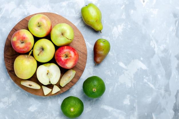 トップビュー新鮮なリンゴ熟したまろやかな果物とみかんと梨ライトホワイトの机の上に