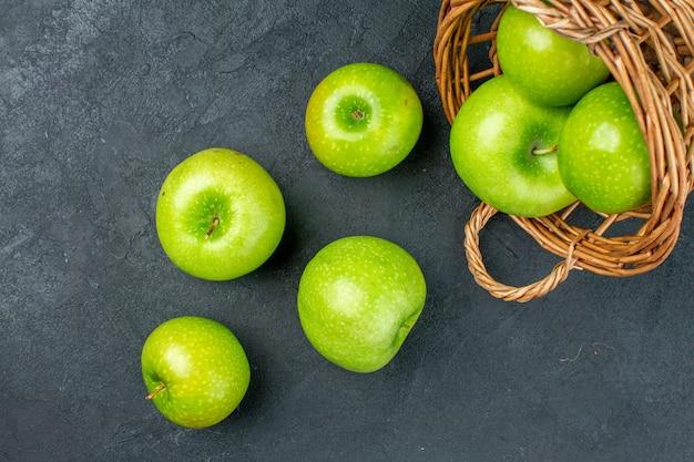 暗い表面の籐のバスケットから散らばっている上面図新鮮なリンゴ