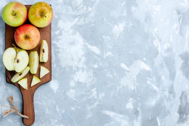 Vista dall'alto mele fresche affettate frutti interi sulla superficie bianco chiaro