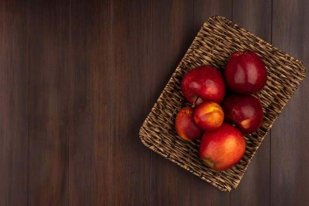 Top view of fresh apples on a wicker tray on a wooden wall with copy space