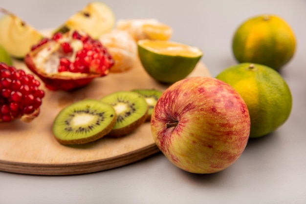 Vista dall'alto di mele fresche con frutta come mele kiwi melograno su una tavola di cucina in legno