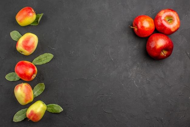 Vista dall'alto mele fresche con foglie verdi sul tavolo scuro fresco e maturo