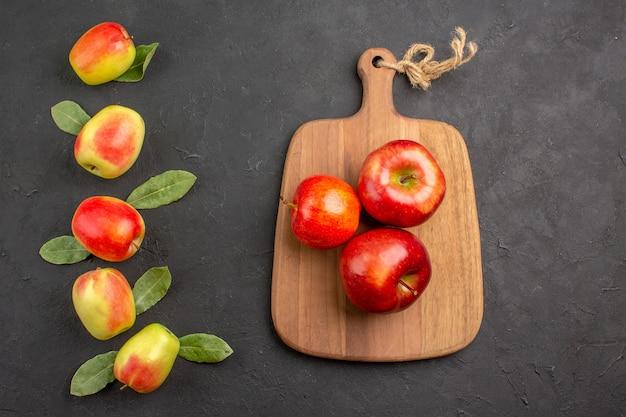 暗いテーブルに緑の葉が付いた新鮮なリンゴの上面図まろやかな新鮮な熟した