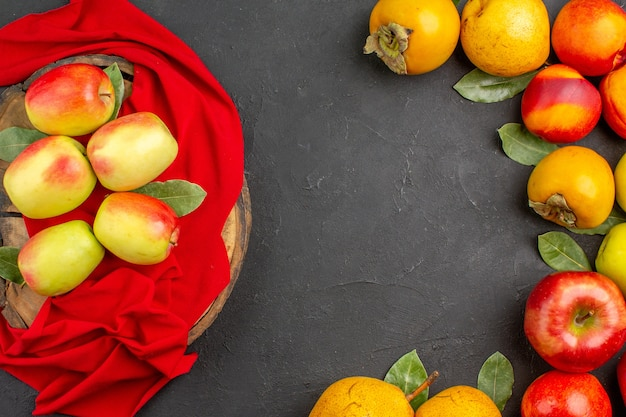 어두운 탁자 나무에 있는 다른 과일과 함께 신선한 사과가 신선하게 잘 익었습니다.