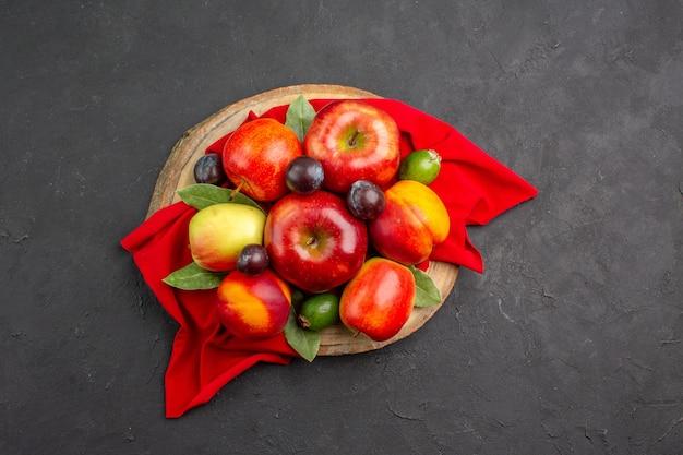 暗いテーブルの上の桃とプラムと新鮮なリンゴの上面図熟した果樹まろやかなジュース