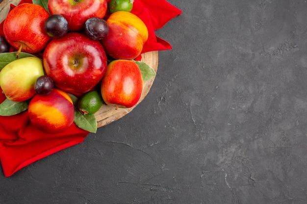 暗いテーブルの上の桃とプラムと新鮮なリンゴの上面図熟した果物の木まろやかなジュース