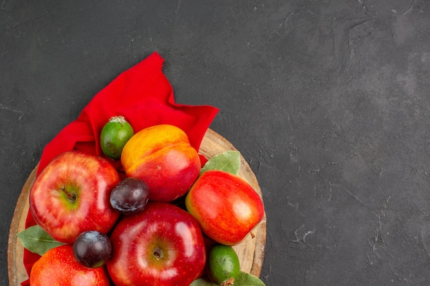 暗いテーブルの果樹のまろやかなジュースに桃とプラムとトップビューの新鮮なリンゴ