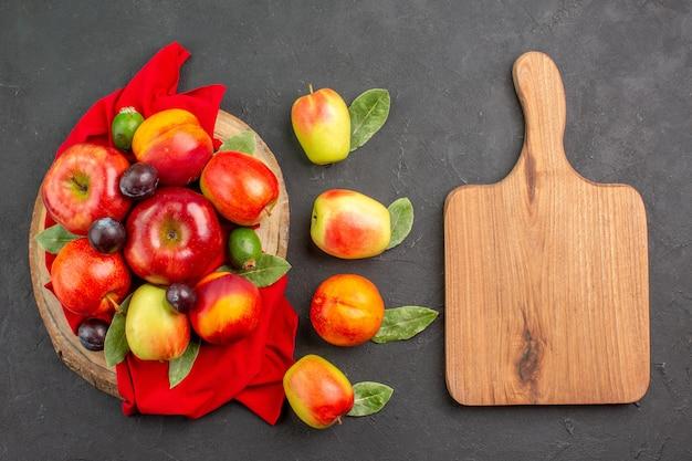 暗いテーブルジュース熟したまろやかな木の桃とプラムとトップビューの新鮮なリンゴ