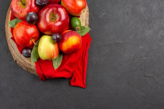 暗いテーブルの熟したフルーツまろやかなジュースの木に桃とプラムと新鮮なリンゴの上面図
