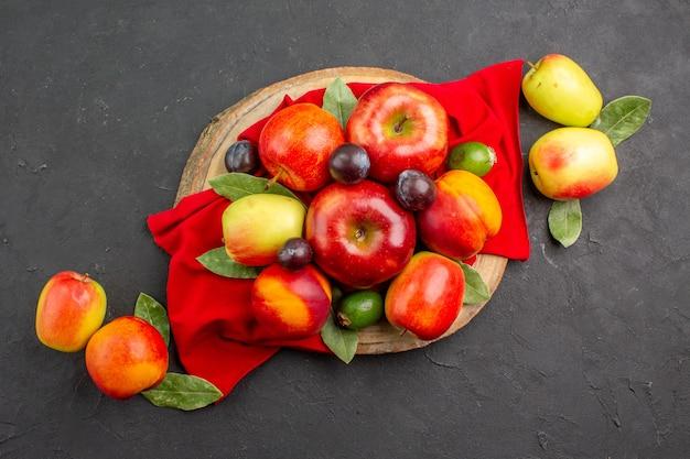 暗いテーブルの熟したまろやかな木の桃とプラムとトップビューの新鮮なリンゴ