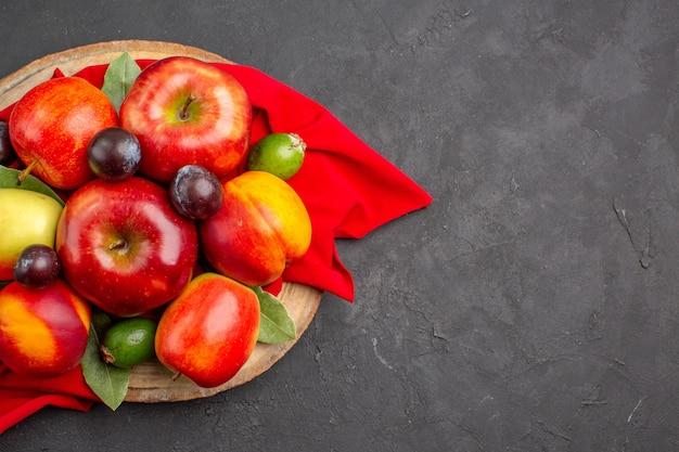 어두운 탁자 위에 복숭아와 자두를 넣은 신선한 사과 잘 익은 과일 나무 부드러운 주스