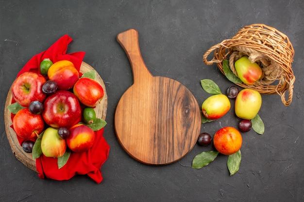 어두운 탁자 위에 있는 복숭아와 자두를 곁들인 신선한 사과