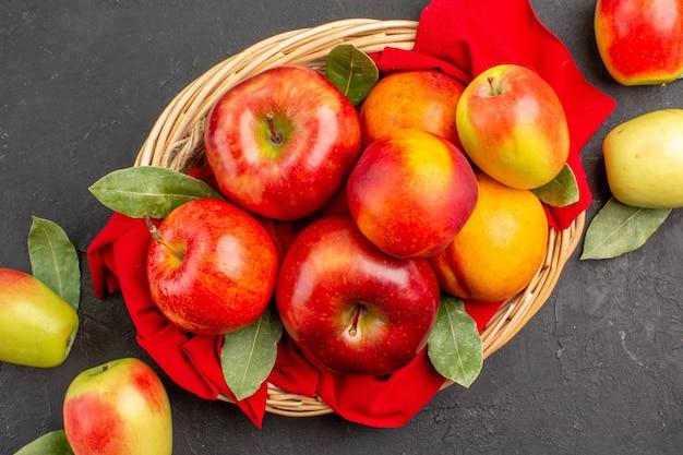 Vista dall'alto mele fresche con pesche sul tavolo scuro succo di frutta matura dolce
