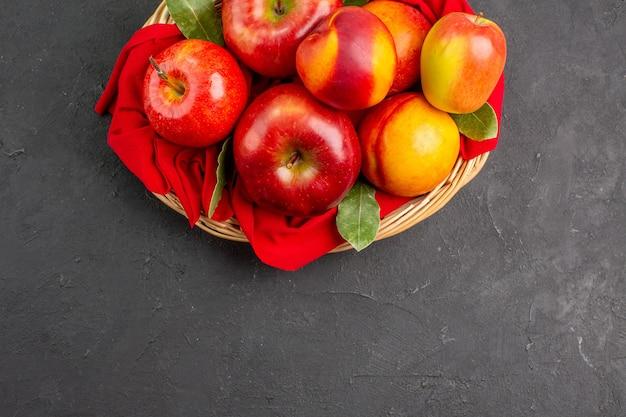 Vista dall'alto mele fresche con pesche all'interno del cesto sul tavolo scuro frutta fresca matura