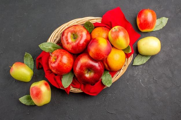 Vista dall'alto mele fresche con pesche all'interno del cesto su tavola scura frutta matura albero fresco