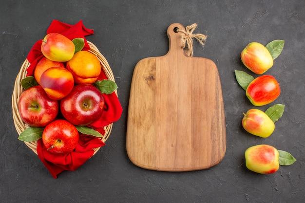 暗い床の新鮮な果樹のバスケットの中に桃と熟した新鮮なリンゴの上面図