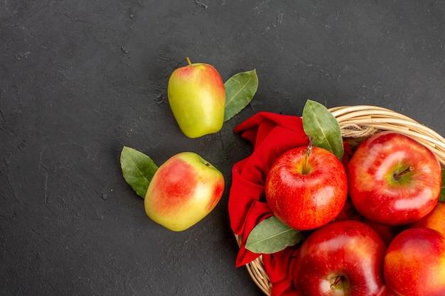 暗い床のバスケットの中に桃が入った新鮮なリンゴの上面図熟した果実の新鮮な