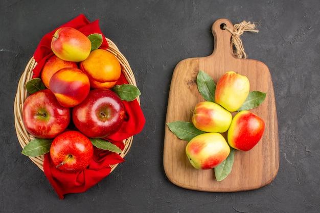 暗いテーブルの上のバスケットの中に桃と新鮮なリンゴの上面図新鮮な果物の木が熟している