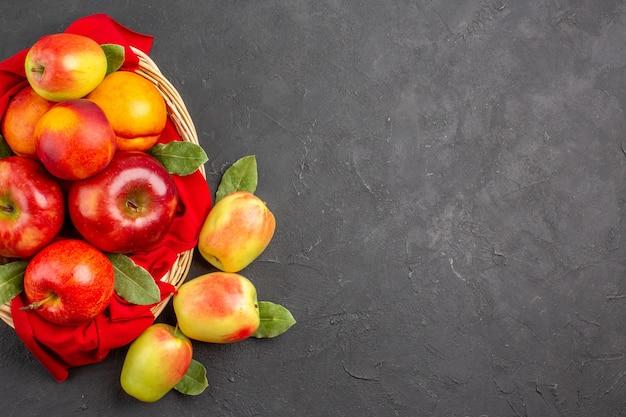 暗いテーブルの上のバスケットの中に桃が入った新鮮なリンゴの上面図熟した新鮮な果物