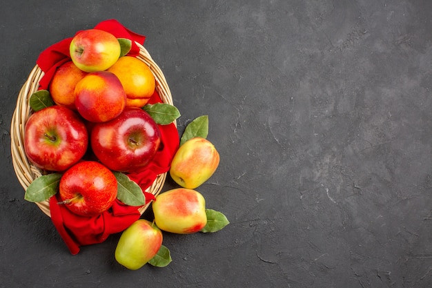 暗いテーブルの果樹のバスケットの中に桃と新鮮な熟した新鮮なリンゴの上面図