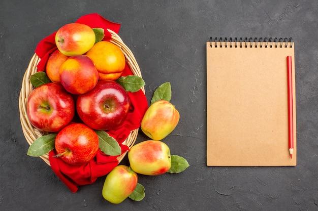 暗いテーブルの上のバスケットの中に桃が入った新鮮なリンゴの上面図果物の木熟した新鮮な