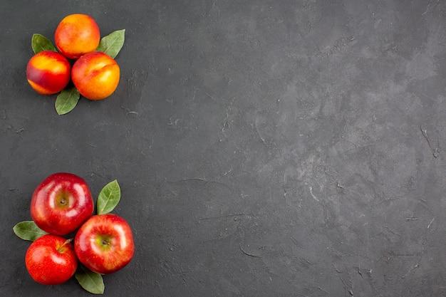 어두운 탁자에 복숭아를 넣은 신선한 사과는 신선하고 잘 익은 과일