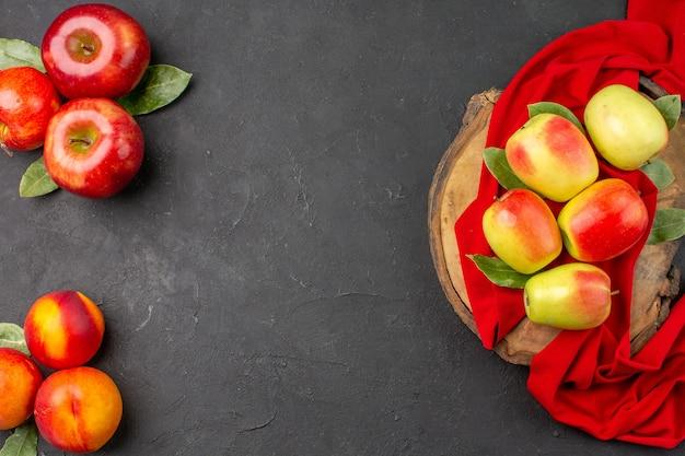 濃い灰色のテーブルの新鮮な果物の色に桃と新鮮なリンゴの上面図
