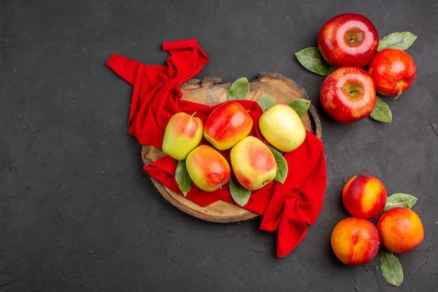 濃い灰色のテーブルの熟した果実の色に桃と新鮮なリンゴの上面図