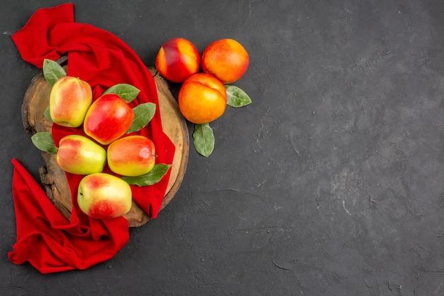 어두운 탁자에 복숭아를 넣은 신선한 사과가 신선하고 잘 익은 과일