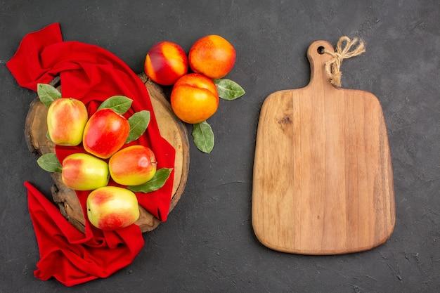 어두운 탁자에 복숭아가 있는 신선한 사과는 신선하고 잘 익은 과일을 색으로 칠합니다.