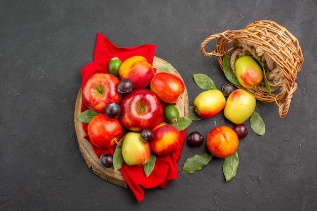 Vista dall'alto mele fresche con pesche e prugne su un albero di succo maturo da scrivania scuro morbido
