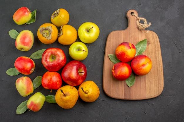 Вид сверху свежие яблоки с хурмой и грушами на темном столе, спелое дерево, свежее спелое