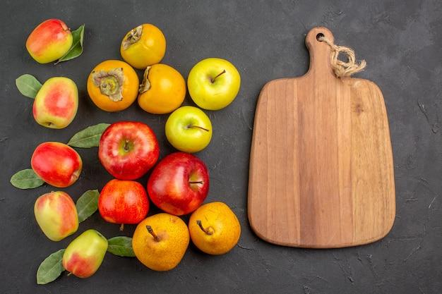 暗いテーブルの上の柿と梨と新鮮なリンゴの上面図まろやかな新鮮な熟した木
