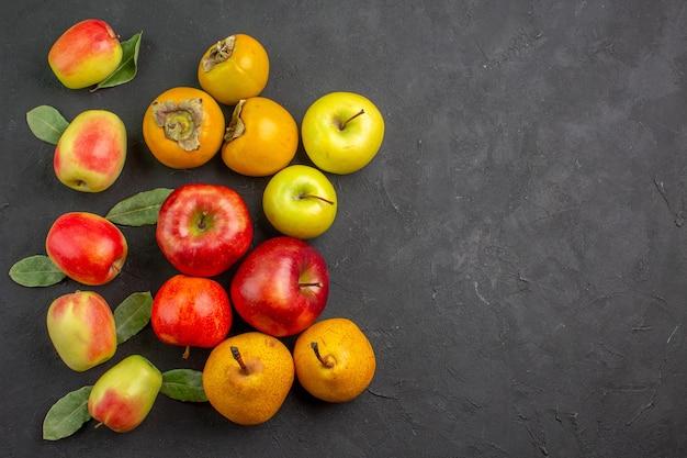 Вид сверху свежие яблоки с хурмой и грушами на темном столе, спелом дереве, свежем спелом