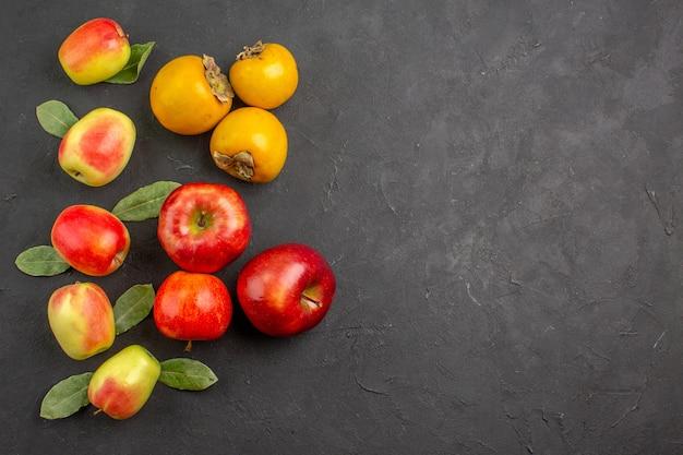 暗いテーブルの上の柿と新鮮なリンゴの上面図まろやかな木新鮮な熟した